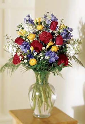 Mostly roses this vibrantly colored memorial bouquet commemorates a life of beauty bursting with glorious shades of red yellow blue and white flowers plus assorted mightylinksfo